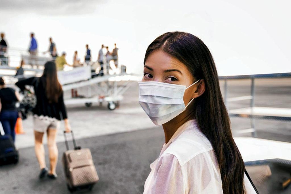 Turista in aeroporto con mascherina Covid-19